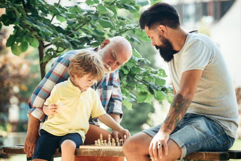 Sports de pratique d'homme plus âgé sur le fond de ciel bleu Jour de p?res Les trois générations heureuses des hommes ont l'amuse image stock