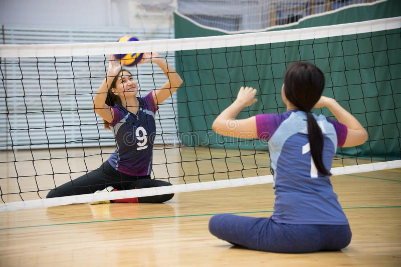 Sports for disabled people. Two young women sitting on the floor and playing volleyball. Smiling stock photos