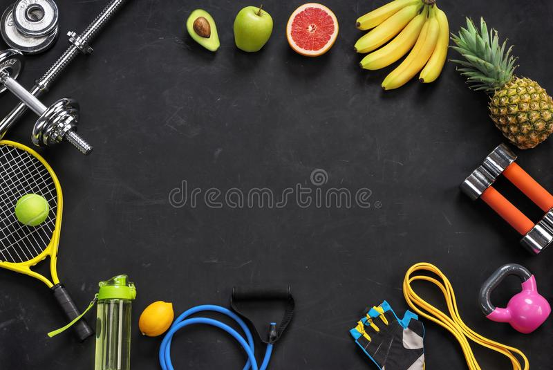 Sports equipment and organic food on black background. Top view. Motivation stock photos