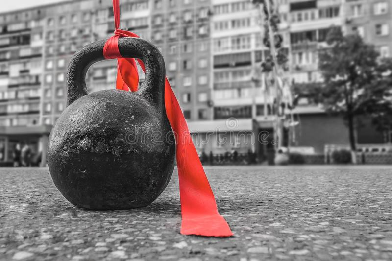 Sports equipment with a red ribbon for bodybuilding is on the asphalt during a sports holiday royalty free stock photo