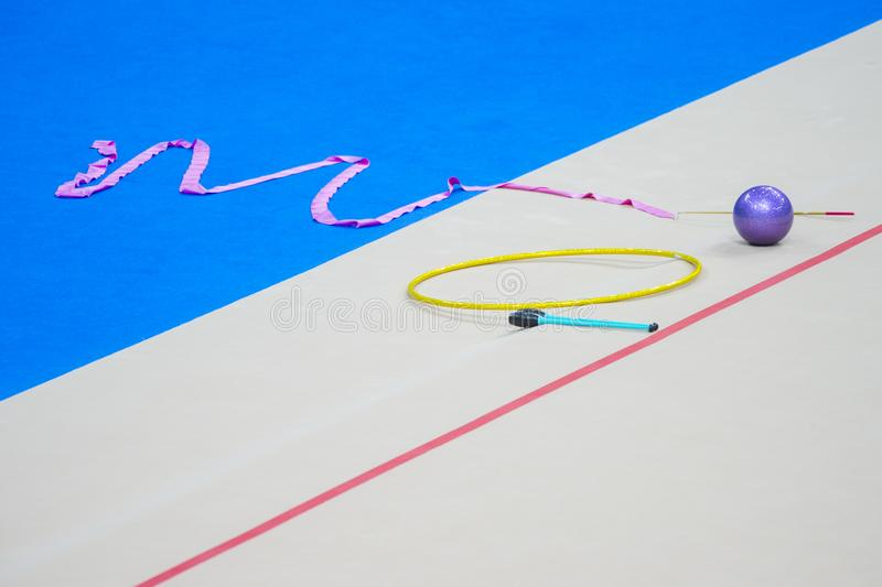 Sports equipment for rhythmic gymnastics lie on the edge of the carpet in the gym. Rhythmic gymnastics clubs, a ball, a hoop.  royalty free stock images