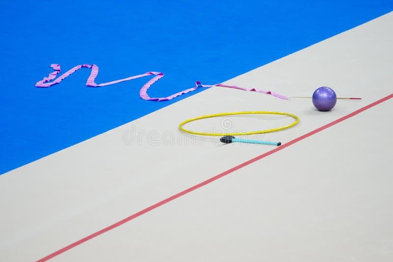 Sports equipment for rhythmic gymnastics lie on the edge of the carpet in the gym. Rhythmic gymnastics clubs, a ball, a hoop.  stock photos