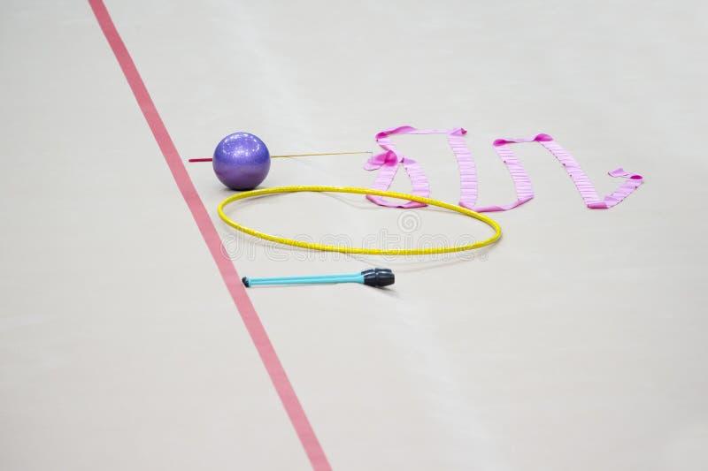 Sports equipment for rhythmic gymnastics lie on the edge of the carpet in the gym. Rhythmic gymnastics clubs, a ball, a hoop.  stock images