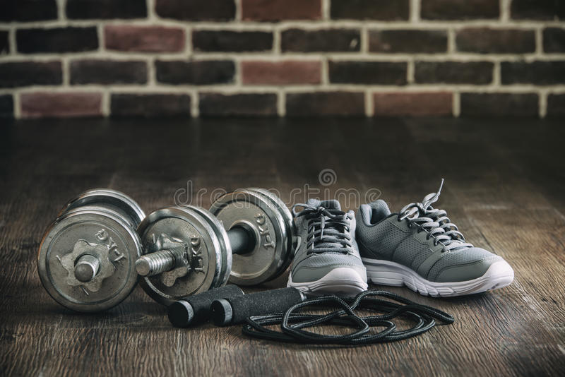 Sports equipment sneakers rope skipping dumbbell for fitness. On wooden floor, brick wall background stock photo