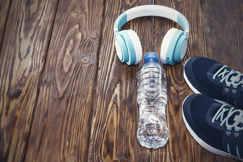 Sports equipment. Sneakers, water and headphones on wooden background.  royalty free stock photography