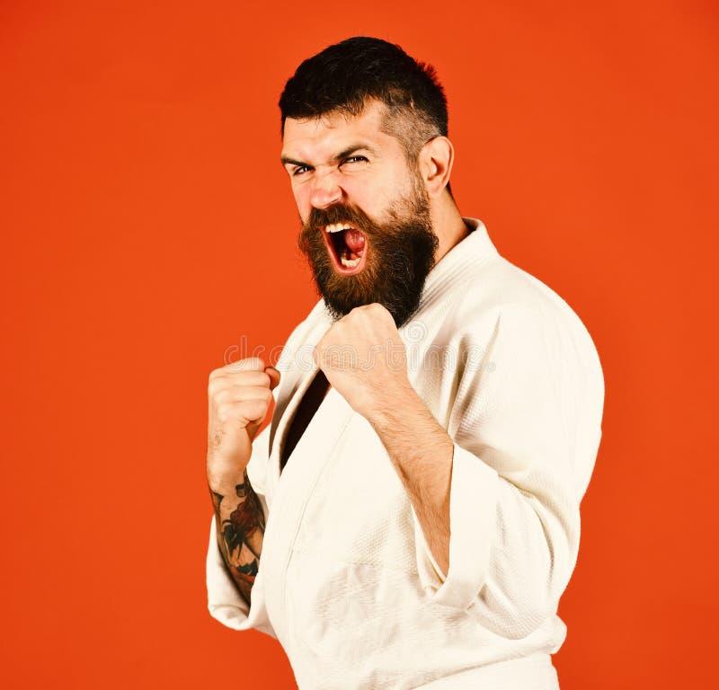 Sports et concept japonais d'arts martiaux Jeune homme sportif dans le kimono blanc d'isolement sur le fond rouge image libre de droits