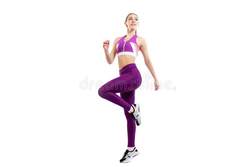 Sports exercises for women. A dark-haired woman coach in a sporty pink short top and gym leggings .doing exercise to warm up the legs, alternate knee flexion  on stock photography