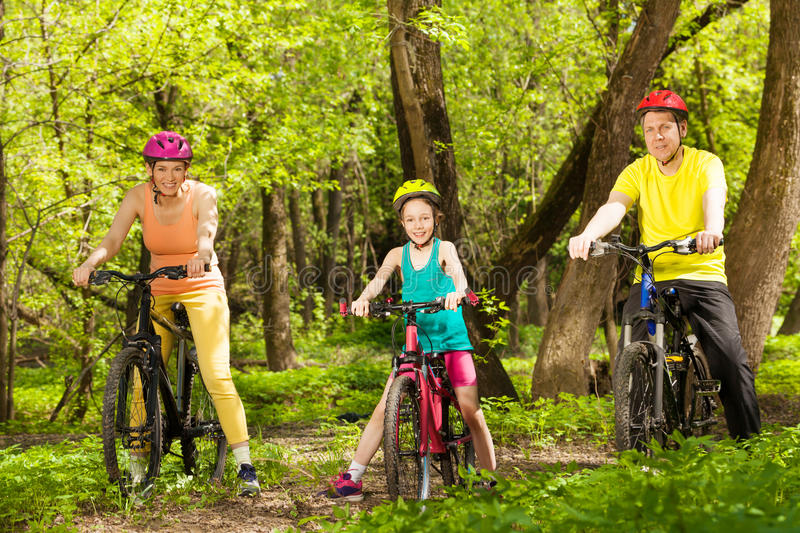 Sports family cycling in the beautiful forest. Picture of sports family, mother, father and teenage girl cycling in the sunny spring forest royalty free stock photo