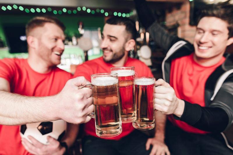 Sports fans celebrating and cheering drinking beer at sports bar. They are supporting red team stock image