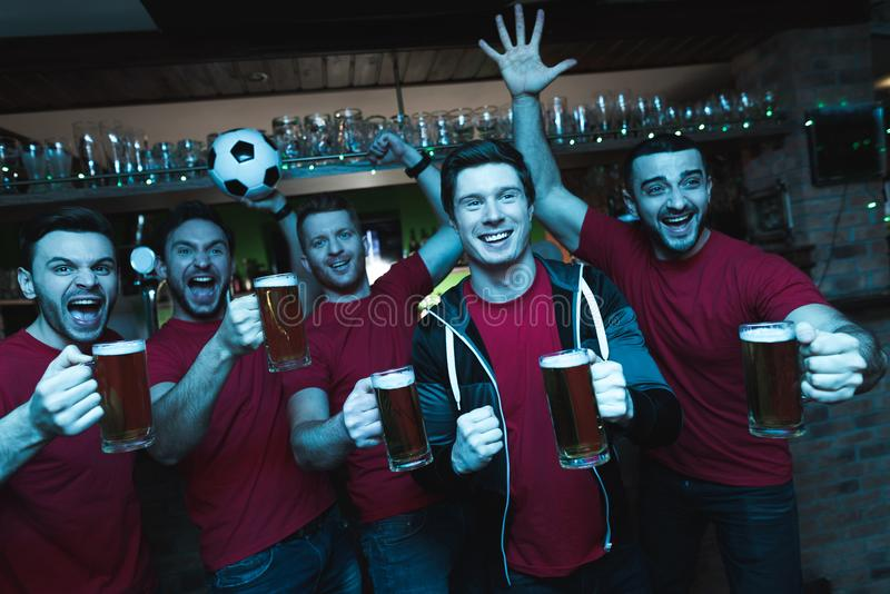 Sports fans celebrating and cheering in front of tv drinking beer at sports bar. They are supporting red team stock images
