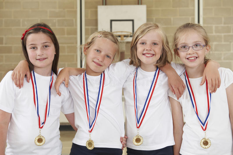 Sports femelles Team In Gym With Medals d'école photo stock