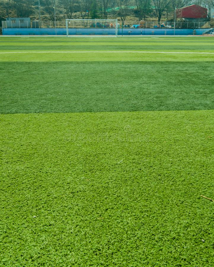 Sports field covered with green artificial grass. With soccer goal in the distance stock photos
