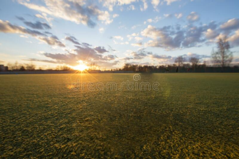 Sports field at sunset. Natural grassy background with field and blue sky stock photos