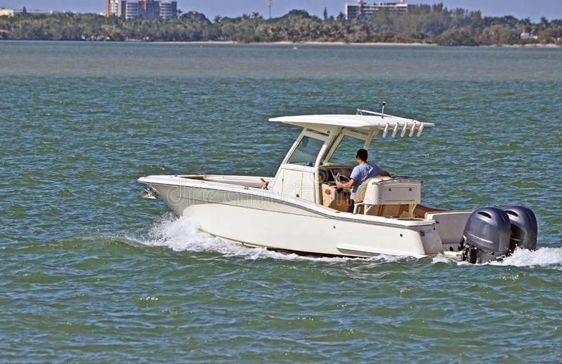 Sports Fishing Boat Cruising on the Florida Intra-Coastal Waterway. Small sport fishing boat powered by two outboard engines cruising on the florida intra royalty free stock image