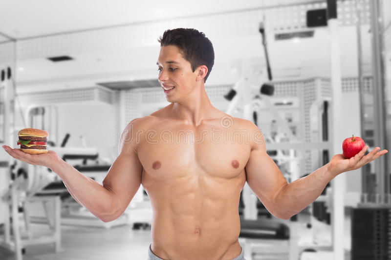 Sports fit diet apple fruit hamburger healthy eating fitness gym. Bodybuilder bodybuilding young man studio royalty free stock photo