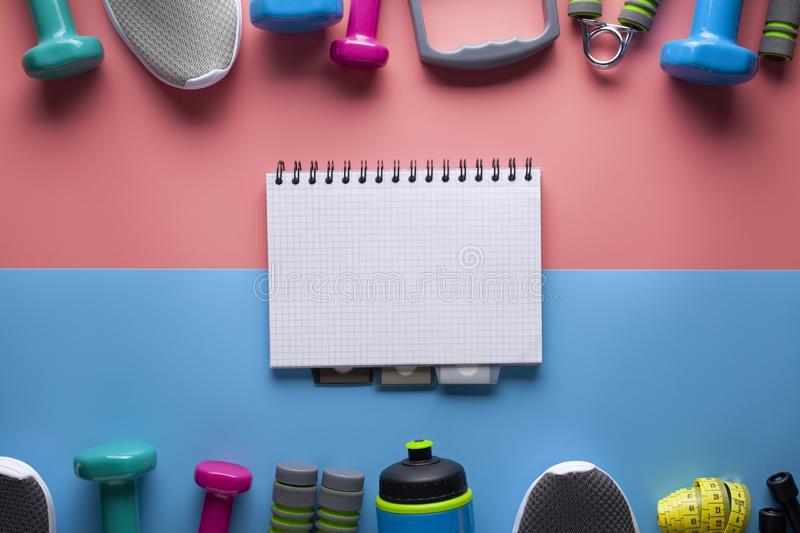 Sports and fitness equipment and classic paper notebook with a blank page on colored background stock image
