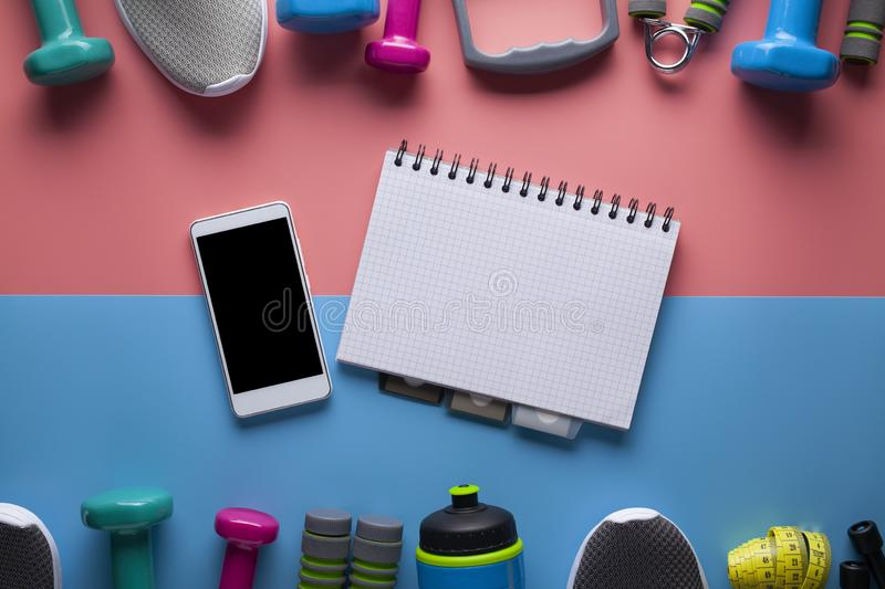 Sports and fitness equipment, modern mobile phone and classic paper notebook with a blank page on a colored background stock photography