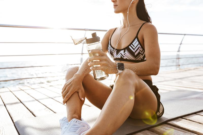 Sports fitness woman drinking water at the beach outdoors listening music with earphones. Cropped image of a beautiful young sports fitness woman drinking water royalty free stock image