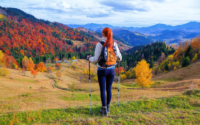 A sports girl with a backpack and tourist sticks. stock photography