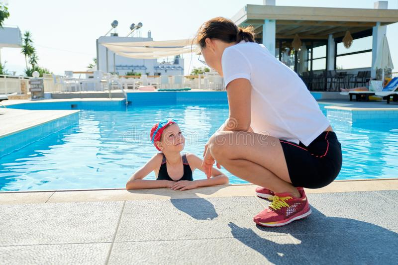 Sports girl child in swimsuit cap glasses in pool talking with mother stock images