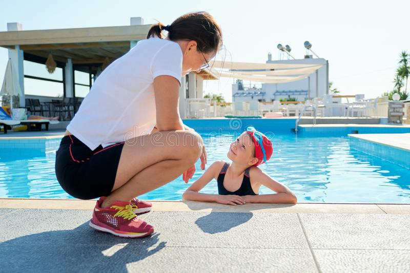 Sports girl child in swimsuit cap glasses in pool talking with mother stock image