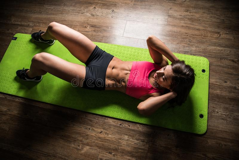 Sports girl does crunches while lying on a press on the green Mat in the fitness room. royalty free stock photo