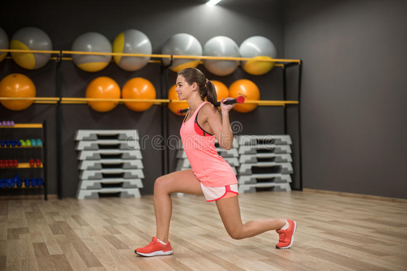 A sports girl doing leg exercises on a gym background. Fit young female with a fitness stick. Building muscles concept. An athletic young woman exercising with stock image