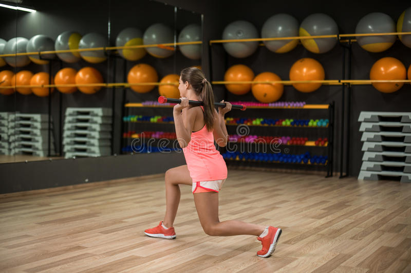 A sports girl doing leg exercises on a gym background. Fit young female with a fitness stick. Building muscles concept. An athletic young woman exercising with royalty free stock photos