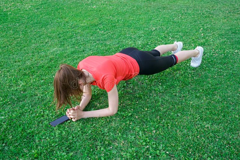 Sports girl doing planking on the lawn royalty free stock images