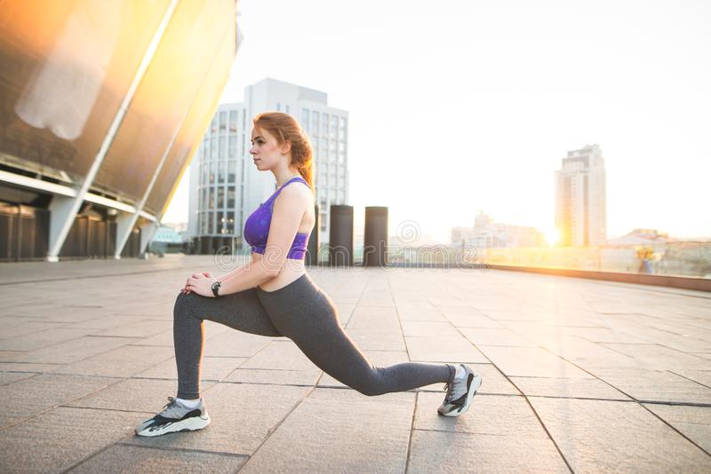 Sports girl doing stretching, warming up before training. Fitness girl in sports wear stretches on training. Morning sports on the background of the city in stock image