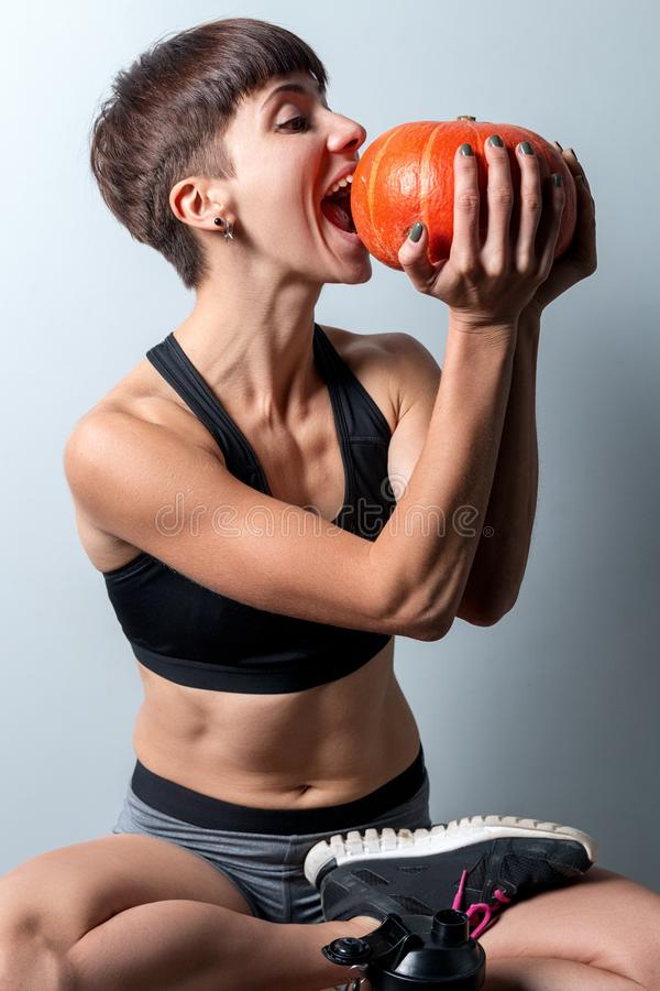 Sports girl doing yoga with a pumpkin on a holiday of halloween stock images