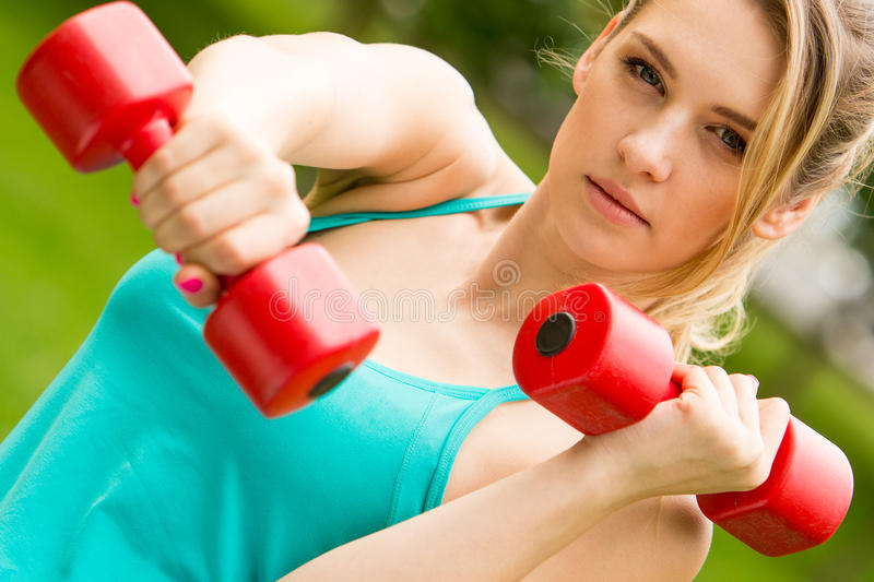 Sports girl exercise with dumbbells in the park stock images