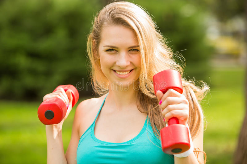 Sports girl exercise with dumbbells in the park royalty free stock photos