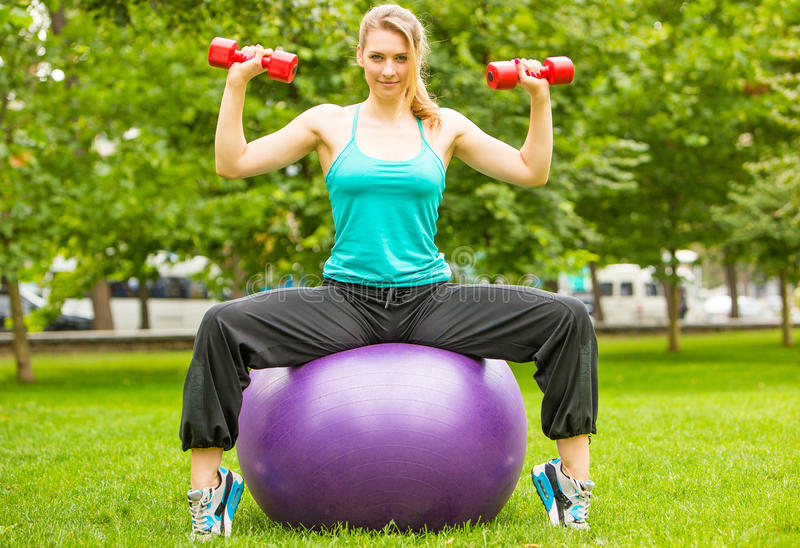 Sports girl exercise with dumbbells in the park stock image