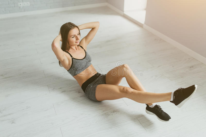 Sports girl in fitness training and doing press in a bright room royalty free stock photos