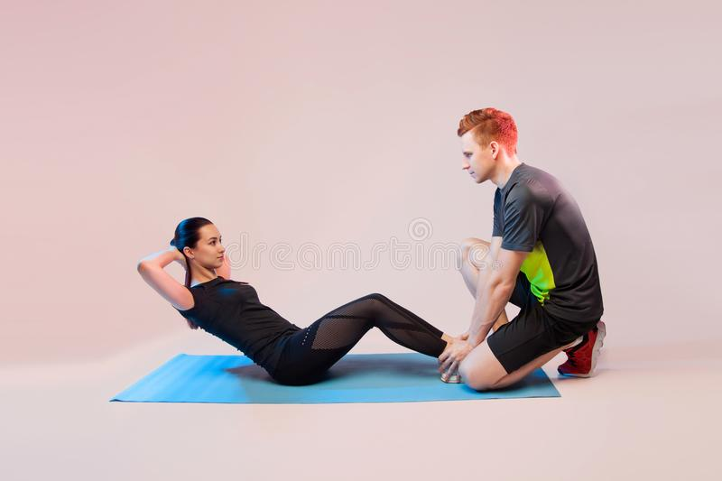 Sports girl and guy doing exercises. He helps the girl to rock the press. On a light background, a place for text royalty free stock photos