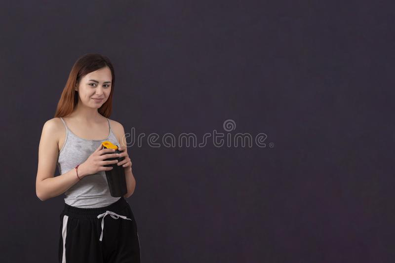 Sports girl after playing sports drinks from a shaker with a wet shirt from sweat copyspace royalty free stock image