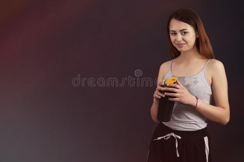 Sports girl after playing sports drinks from a shaker with a wet shirt from sweat copyspace royalty free stock images