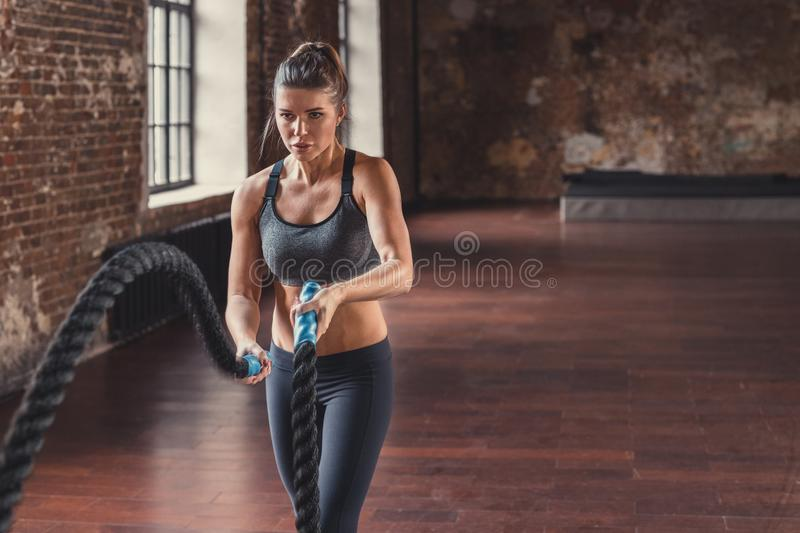 Sports girl with a rope in the loft. Sports young girl with a rope in the loft royalty free stock photos