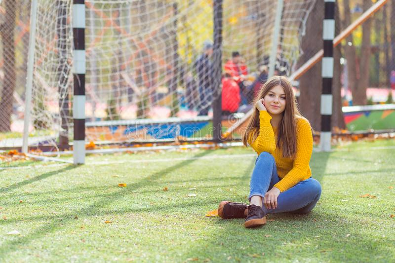 Sports girl sits on the grass on the football field stock images