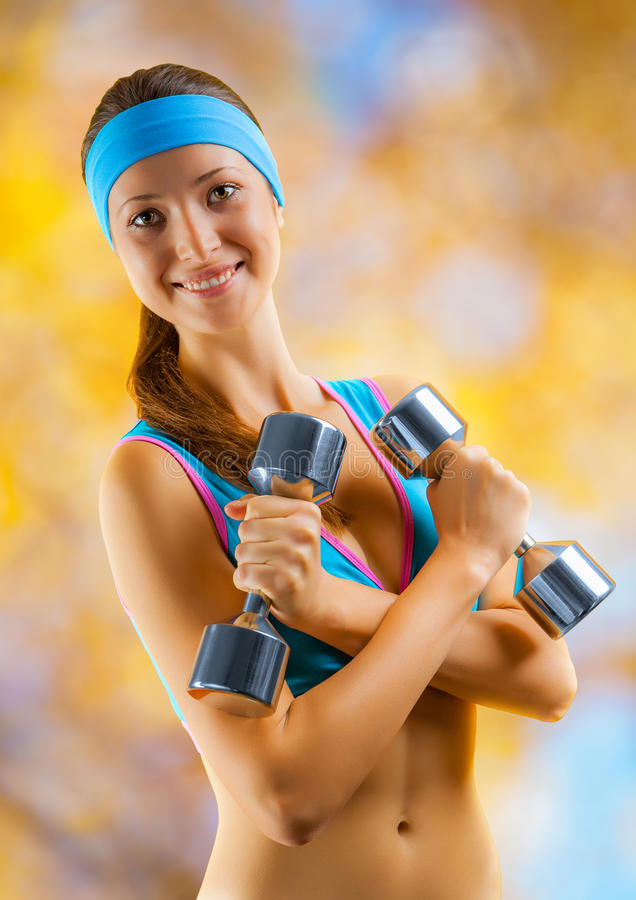 A sports girl with two dumbbells