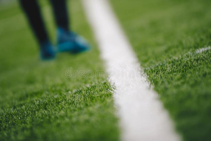 Sports grass field pitch and white sideline. Sports player walking in the blurred background royalty free stock photo