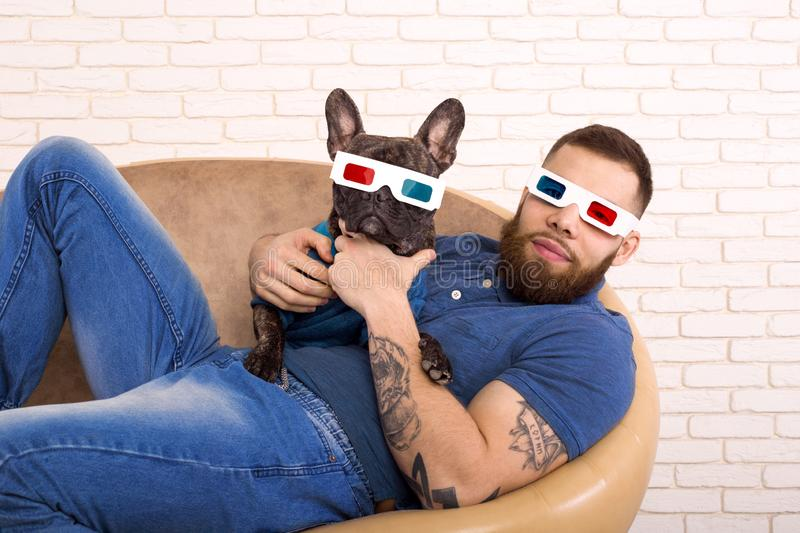 Sports guy in 3D glasses with his dog lying on the couch stock images