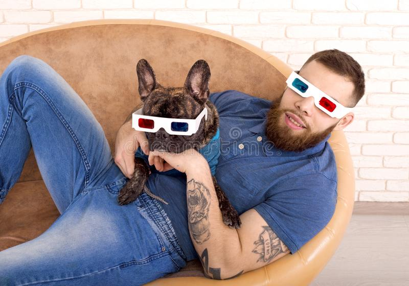 Sports guy in 3D glasses with his dog lying on the couch royalty free stock photography