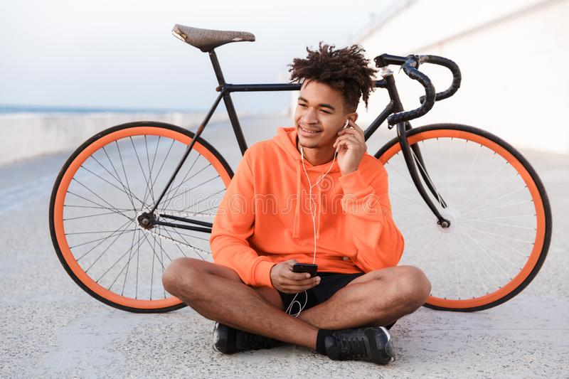 Sports guy outdoors on the beach with bicycle using mobile phone listening music. Image of a young sports guy outdoors on the beach with bicycle using mobile royalty free stock image