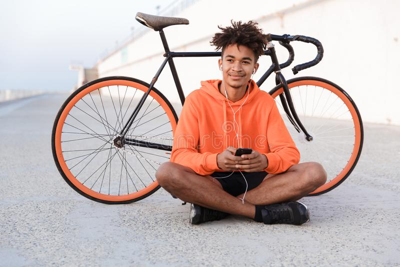 Sports guy outdoors on the beach with bicycle using mobile phone listening music. Image of a young sports guy outdoors on the beach with bicycle using mobile stock image