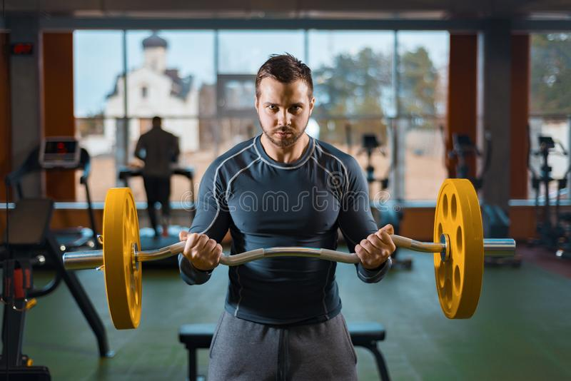 Sports guy is training with a barbell. athletic man doing weight training in the gym. Sports guy is training with a barbell. athletic man doing weight in the stock photography
