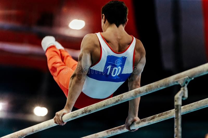 Gymnast exercises on parallel bars. Sports gymnastics athlete gymnast exercises on parallel bars stock photos