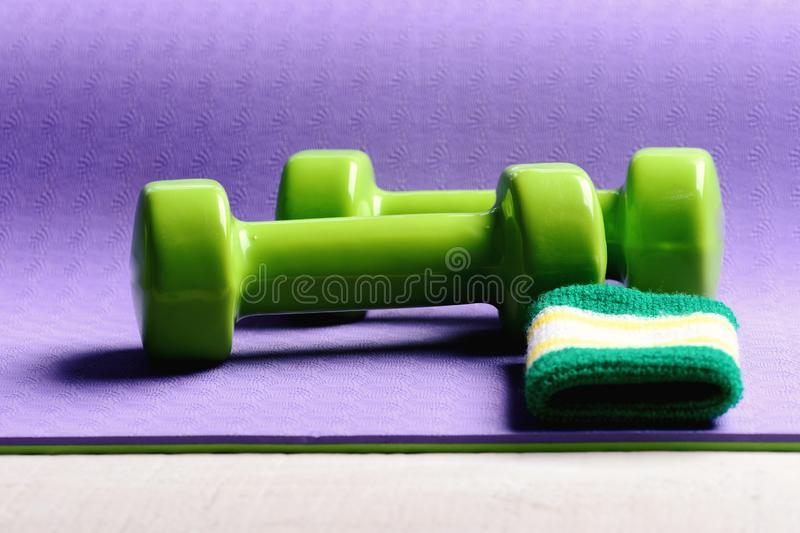 Sports and healthy lifestyle concept. Dumbbells made of green plastic stock photography