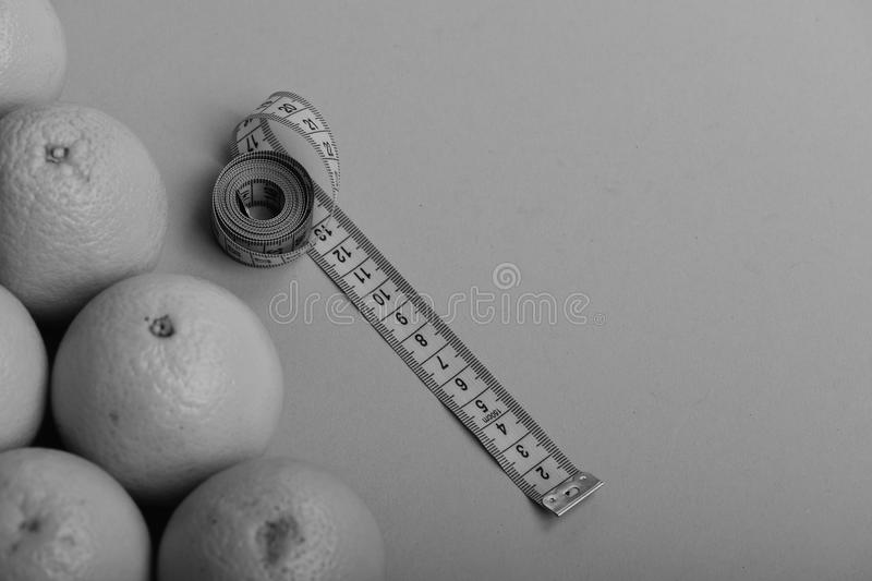 Oranges near long measuring tape on green background, top view stock image